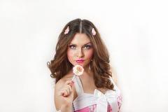 Menina atrativa com um pirulito em seu vestido da mão e do rosa isolado no branco. Morena longa bonita do cabelo que joga com um p Foto de Stock Royalty Free