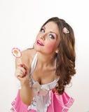 Menina atrativa com um pirulito em seu vestido da mão e do rosa isolado no branco. Morena longa bonita do cabelo que joga com um p Imagem de Stock Royalty Free