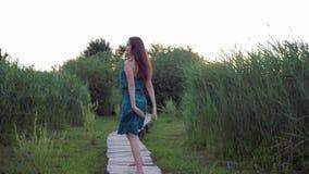 A menina atrativa corre com os pés descalços no ar livre da ponte de madeira e natureza da apreciação entre a grama verde alta vídeos de arquivo