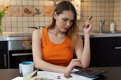 Menina atrativa da jovem mulher que senta-se no funcionamento da mesa de cozinha imagem de stock
