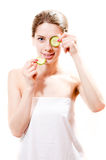 Menina atrativa da mulher bonita nova dos termas que está com fatias de pepino nas mãos uma parte no olho isolado Fotografia de Stock Royalty Free