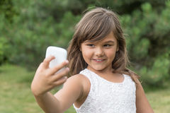 A menina atrativa de sorriso está fazendo o selfie Fotografia de Stock