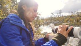 A menina atrativa do caminhante senta-se perto do lago do norte e bebe-se o chá quente de uma garrafa térmica 4K, Slowmotion video estoque