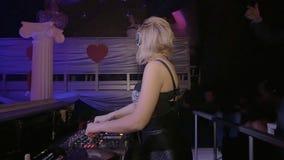 Menina atrativa do DJ nos fones de ouvido que misturam na plataforma giratória nightclub Movimento lento video estoque
