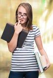 Menina atrativa do estudante nos monóculos com livros Imagens de Stock Royalty Free