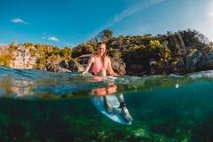 Menina atrativa do surfista com prancha O surfista senta-se na placa imagem de stock