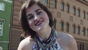 A menina atrativa do vocalista executa na cidade velha no vestido do verão video estoque