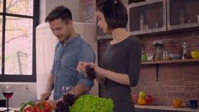 A menina atrativa e o indivíduo considerável cozinham e falam no apartamento vídeos de arquivo