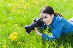 A menina atrativa em um prado toma imagens das flores fotografia de stock royalty free