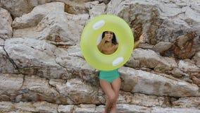 A menina atrativa em um roupa de banho e em um chapéu é faz uma torção engraçada de um círculo inflável do flutuador em sua mão e filme