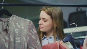 A menina atrativa escolhe um entre duas blusas filme