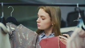 A menina atrativa escolhe um entre duas blusas video estoque