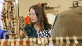 A menina atrativa escolhe vestidos à moda de cores diferentes vídeos de arquivo
