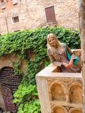 A menina atrativa está estando no balcão de Juliet em Verona Imagens de Stock Royalty Free