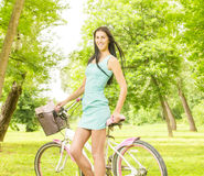 Menina atrativa feliz com bicicleta Fotografia de Stock Royalty Free