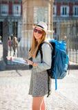 Menina atrativa feliz do estudante de troca que tem o divertimento no guia de visita do turista da leitura da cidade do Madri da  fotografia de stock