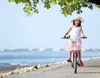 Menina atrativa feliz do litte que veste uma bicicleta da equitação do chapéu exterior foto de stock
