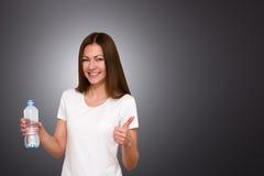 Menina atrativa feliz que está sobre o fundo cinzento e que olha a câmera Foto de Stock