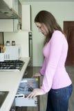 Menina atrativa na blusa cor-de-rosa na cozinha Fotos de Stock Royalty Free