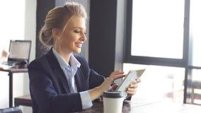 A menina atrativa no terno de negócio usa a tabuleta que senta-se na cafetaria A senhora do negócio está desenvolvendo uma estrat video estoque