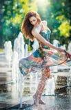 Menina atrativa no vestido curto colorido que joga com água em um dia o mais quente do verão Menina com vestido molhado que aprec Imagens de Stock