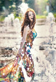 Menina atrativa no vestido curto colorido que joga com água em um dia o mais quente do verão Menina com vestido molhado que aprec Foto de Stock