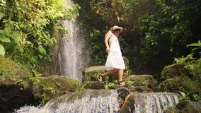 Menina atrativa no vestido e em Straw Hat Walking Barefoot brancos perto da cachoeira pequena na selva tropical da floresta úmida vídeos de arquivo