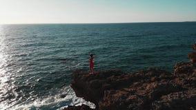 Menina atrativa no vestido vermelho no litoral rochoso Senhora na posição vermelha do vestido em penhascos Menina que olha o por  filme