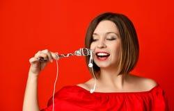 Menina atrativa no vestido vermelho que guarda uma forquilha nas mãos na tomada do fones de ouvido Preparou-se para comer foto de stock royalty free