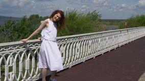 Menina atrativa nos óculos de sol e um vestido branco que andam fora video estoque
