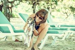 Menina atrativa nova com seu lebreiro do cão de estimação na praia da ilha tropical Bali, Indonésia Momentos felizes Foto de Stock Royalty Free