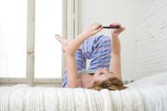 A menina atrativa nova com trabalhos em rede vermelhos do Internet do cabelo com o telefone celular que encontra-se na cama no so Fotografia de Stock