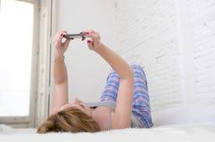 A menina atrativa nova com trabalhos em rede vermelhos do Internet do cabelo com o telefone celular que encontra-se na cama no so Fotos de Stock