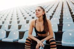 A menina atrativa nova desportiva no sportswear que relaxa após o exercício duro senta e bebe a água da garrafa após a corrida em fotografia de stock royalty free