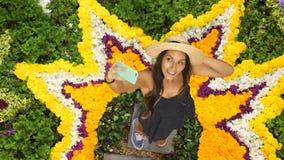 Menina atrativa nova do moderno que faz Selfie usando o telefone celular na composição bonita da flor no fundo 4K filme
