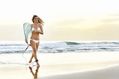 Menina atrativa nova do surfista com a placa que corre fora das ondas Imagens de Stock Royalty Free