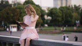 A menina atrativa nova em uma fonte do parque do verão lê um livro com interesse filme