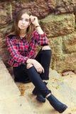Menina atrativa nova encantador bonita com grandes olhos azuis com cabelo longo escuro no dia do outono que senta-se nas escadas Fotografia de Stock Royalty Free