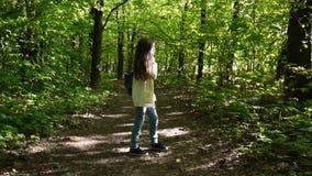 A menina atrativa nova fala usando o telefone que anda no parque Panorama das imagens de vídeo de HD com steadicam video estoque