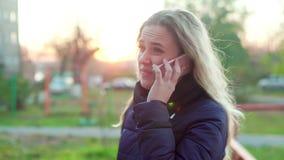 Menina atrativa nova na rua que fala no telefone vídeos de arquivo