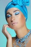 Menina atrativa nova no lenço azul com a pele da saúde e a composição brilhante que tocam em sua face imagem de stock royalty free