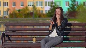 A menina atrativa nova no parque em um banco, recebe SMS, lê-o e ri-o filme