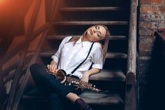 Menina atrativa nova que senta-se em etapas na camisa branca com um saxofone - exterior Jovem mulher 'sexy' com o saxofone que ol Fotos de Stock Royalty Free
