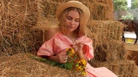 A menina atrativa nova que senta-se em um feno em um chapéu de palha e que sorri, ao lado dela é um ramalhete de flores selvagens video estoque