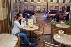 Menina atrativa nova que senta-se na noite em um café com um copo do chá ao contexto de passar carros e vida urbana Olha Fotos de Stock Royalty Free
