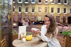 Menina atrativa nova que senta-se na noite em um café com um copo do chá ao contexto de passar carros e vida urbana Olha fotos de stock