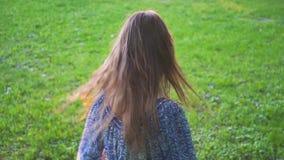 A menina atrativa nova rodopia o cabelo no close up do parque Movimento lento filme