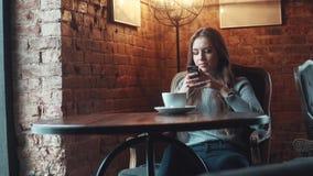 A menina atrativa nova senta-se em um café acolhedor e usa-se um telefone celular vídeos de arquivo