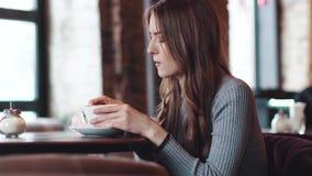 A menina atrativa nova senta-se em um café acolhedor e usa-se um telefone celular video estoque