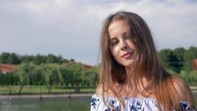 A menina atrativa olha a câmera na luz solar, cabelo marrom dos sopros do vento no fundo da paisagem bonita video estoque